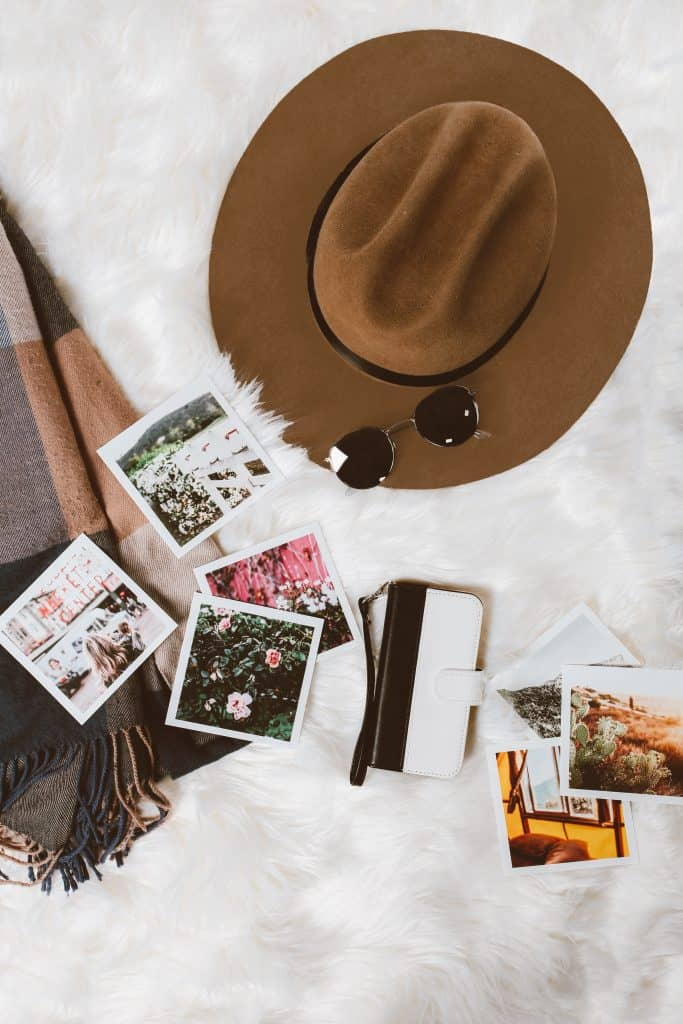 flatlay social media content with polaroids scarf and cowboy hat on white fuzzy rug