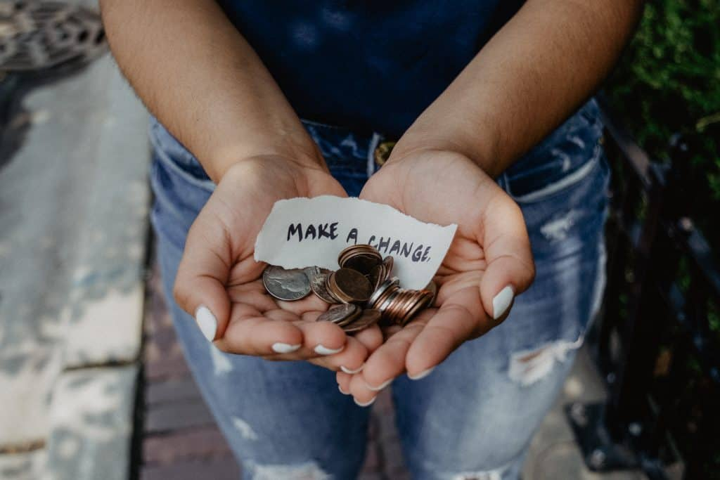 photo of a womans hands with coins in them and a peice of paper that says make a change