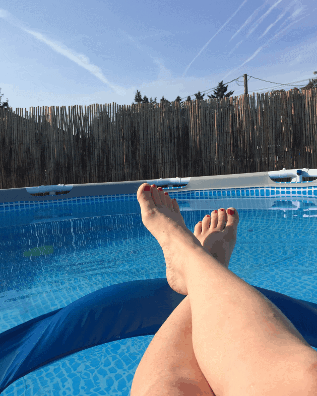 photo of womans legs on intertube in pool on a sunny day in oregon