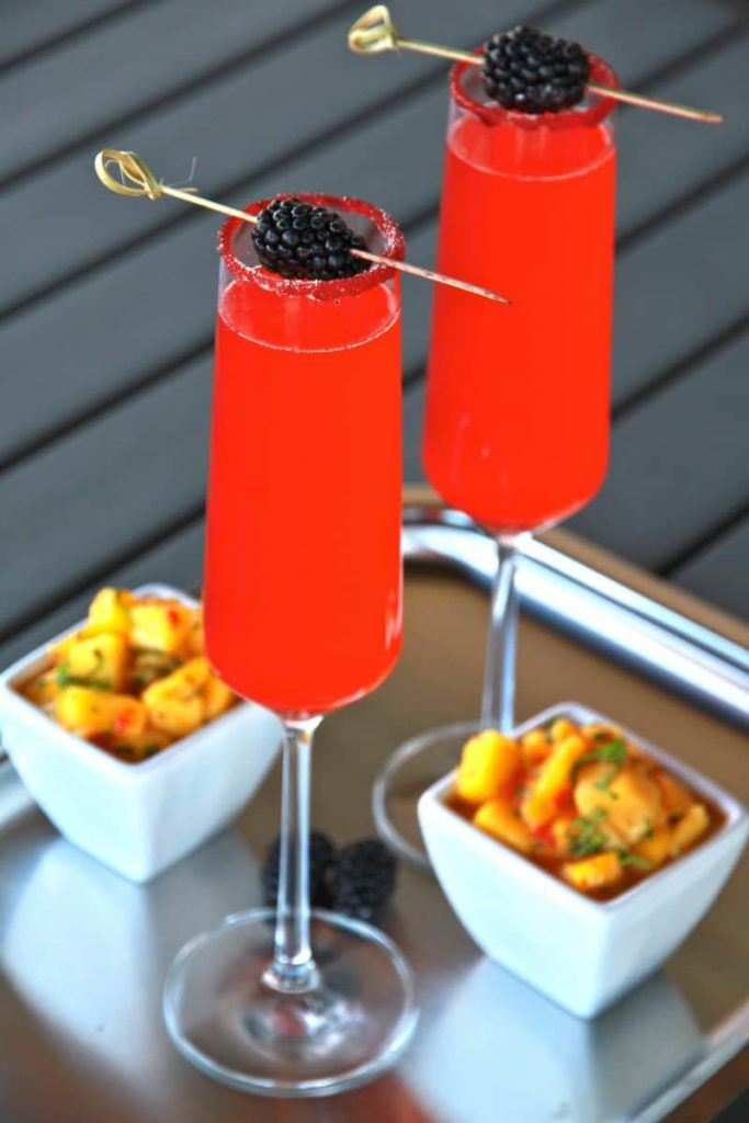 photo of thin tall glasses with red liquid in them and blackberries skewered on top